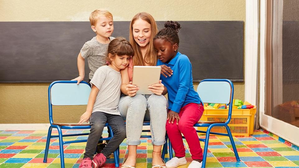 Leraar leest voor van een tablet aan haar leerlingen.