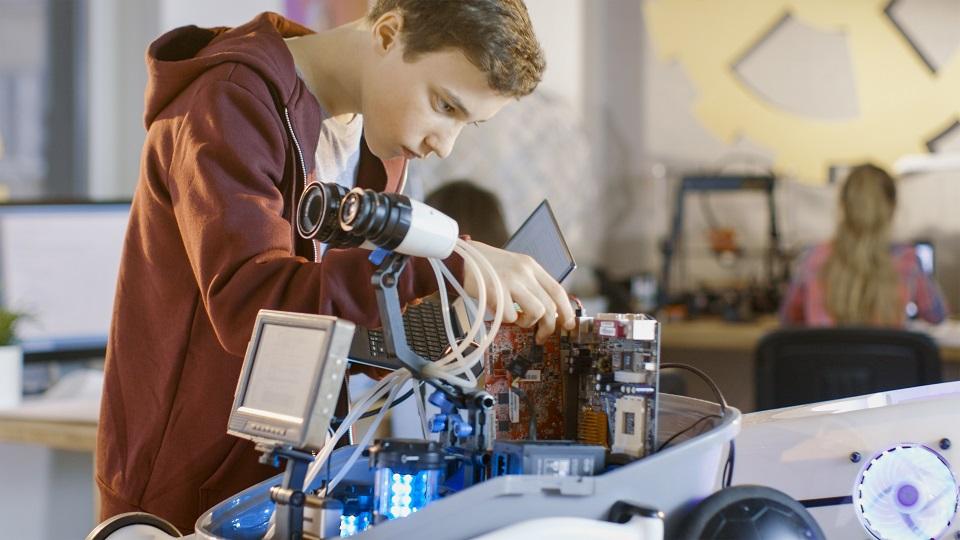 jongen werkt aan een robot voor een robotica-project op school