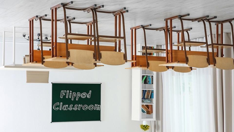 klaslokaal ondersteboven met schoolbanken op de kop aan het plafond. Op schoolbord de tekst 'flipped classroom'