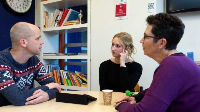 Drie leraren zijn met elkaar in gesprek in de lerarenkamer