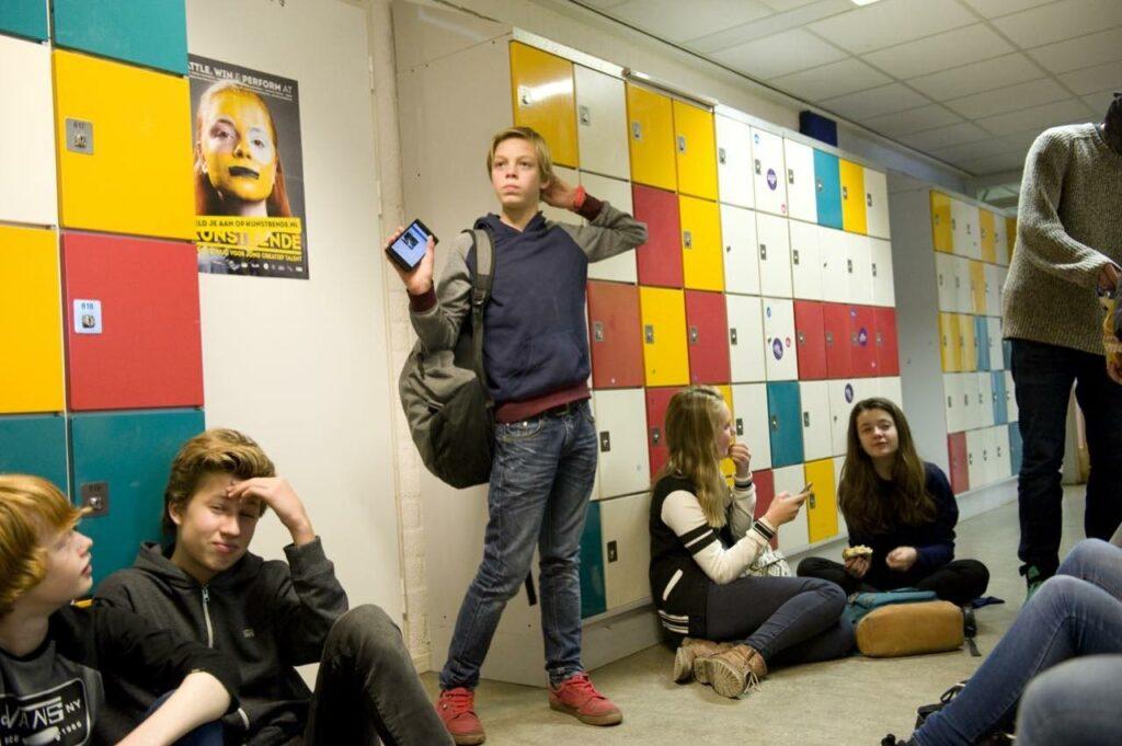 Leerlingen zitten en staan bij gekleurde kluisjes in een schoolgang.