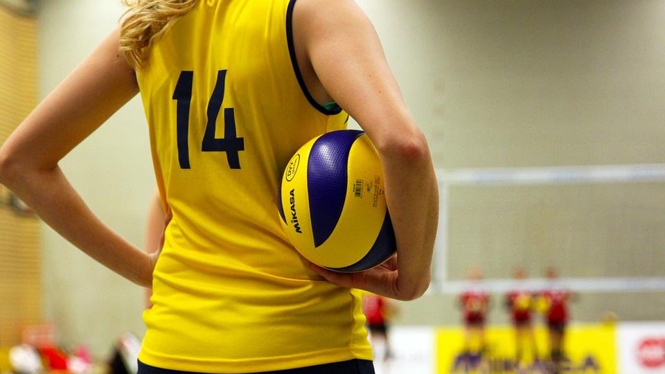 Een leerling die volley speelt heeft staat stil met een bal onder haar arm.