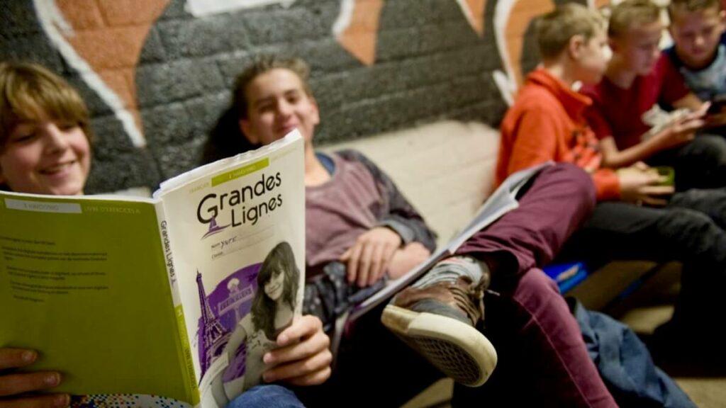 Vijf jongens zitten in de gang met schoolboeken en broodtrommels.