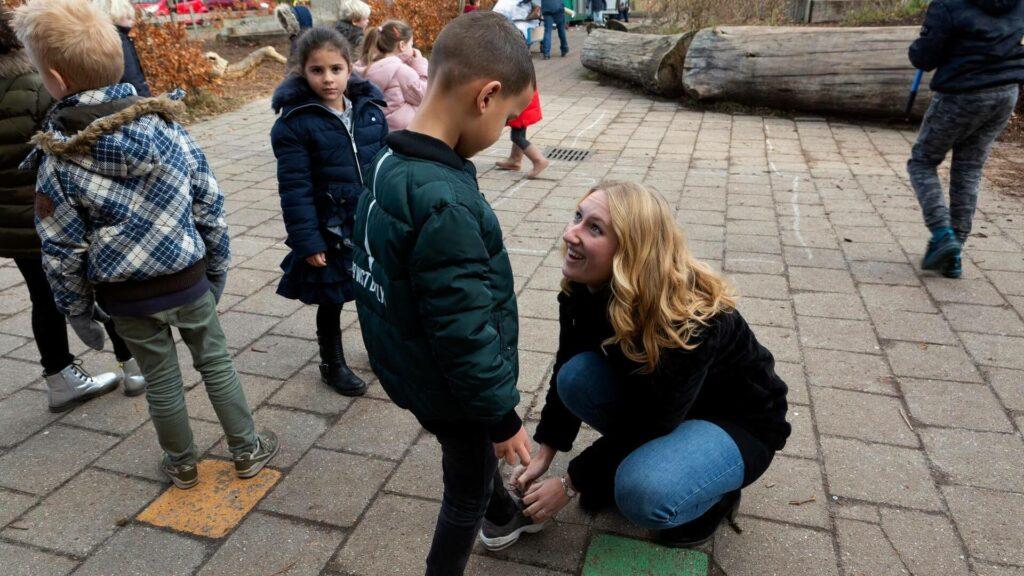 Juf strikt schoen van leerling op het schoolplein