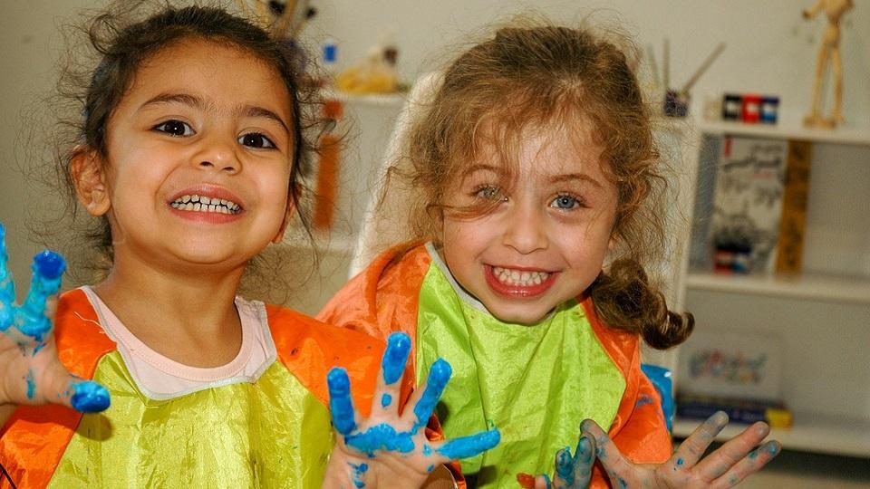 twee blije meisjes in de klas met verf aan hun vingers