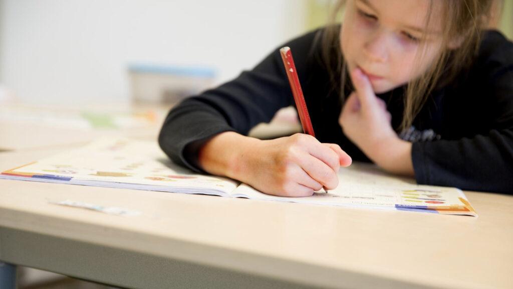 Leerling schrijft in een schrift