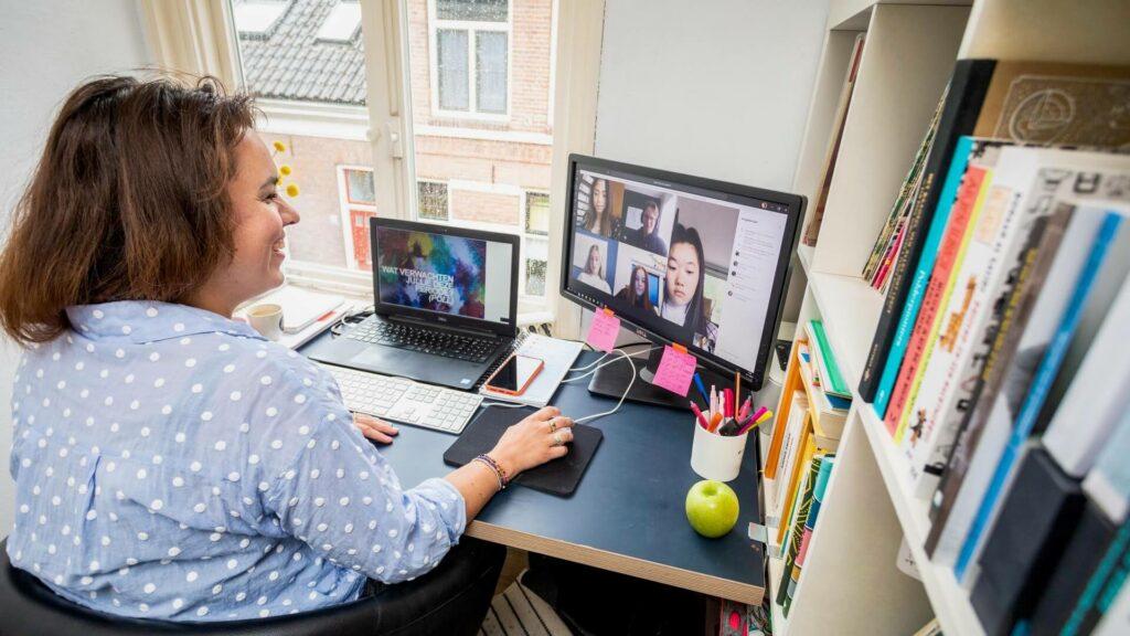 Een docent geeft thuis les op afstand, leerlingen zijn in beeld op haar computerscherm.