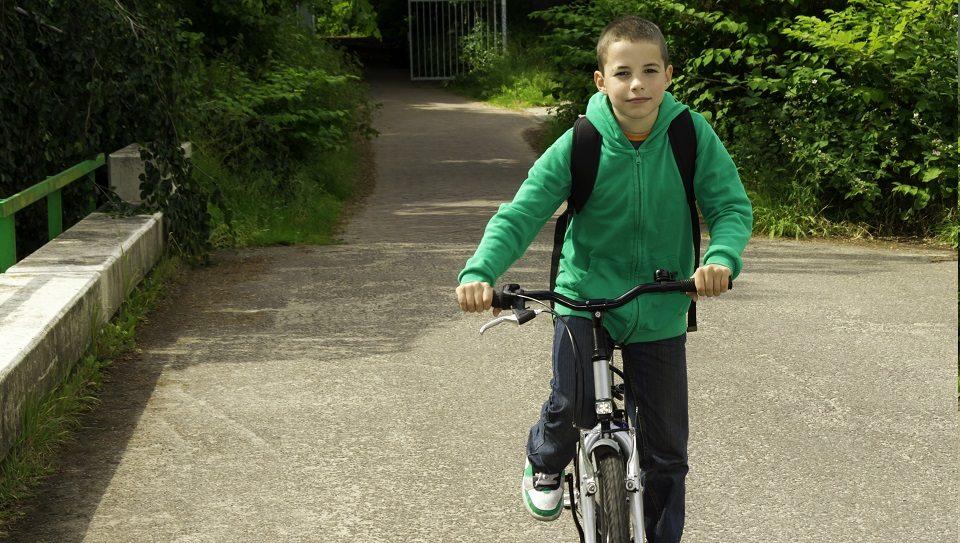 jongen op de fiets op weg naar school