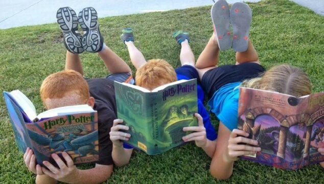 drie kinderen die languit op het gras aan het lezen zijn.