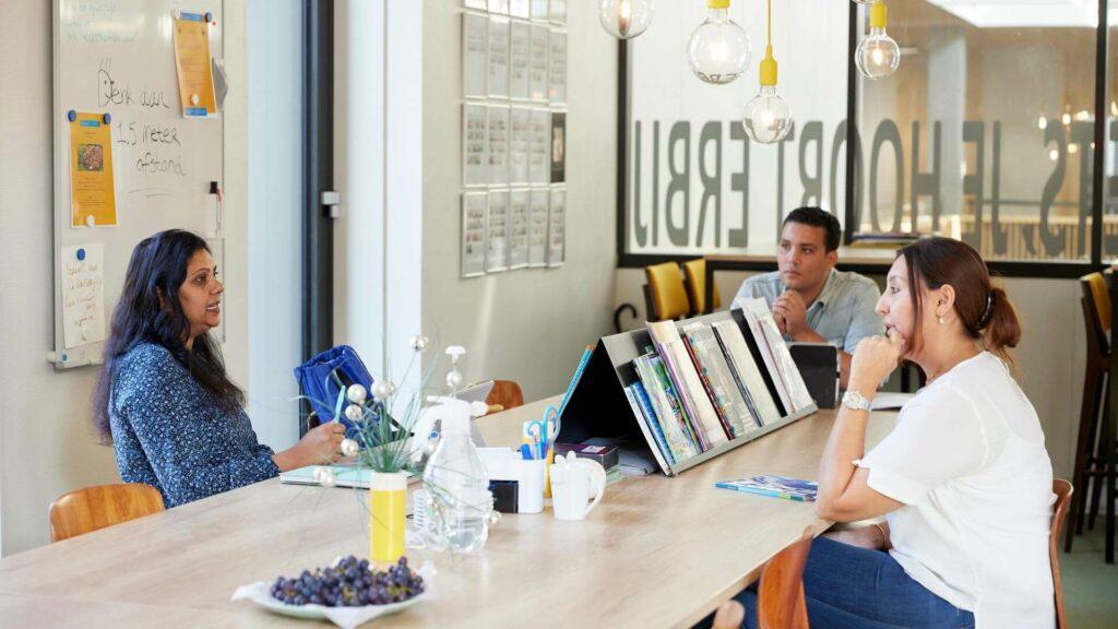 Drie docenten overleggen met elkaar in de lerarenkamer