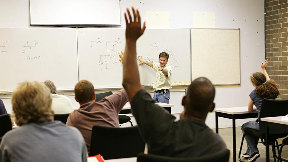 Student steekt hand op in de klas