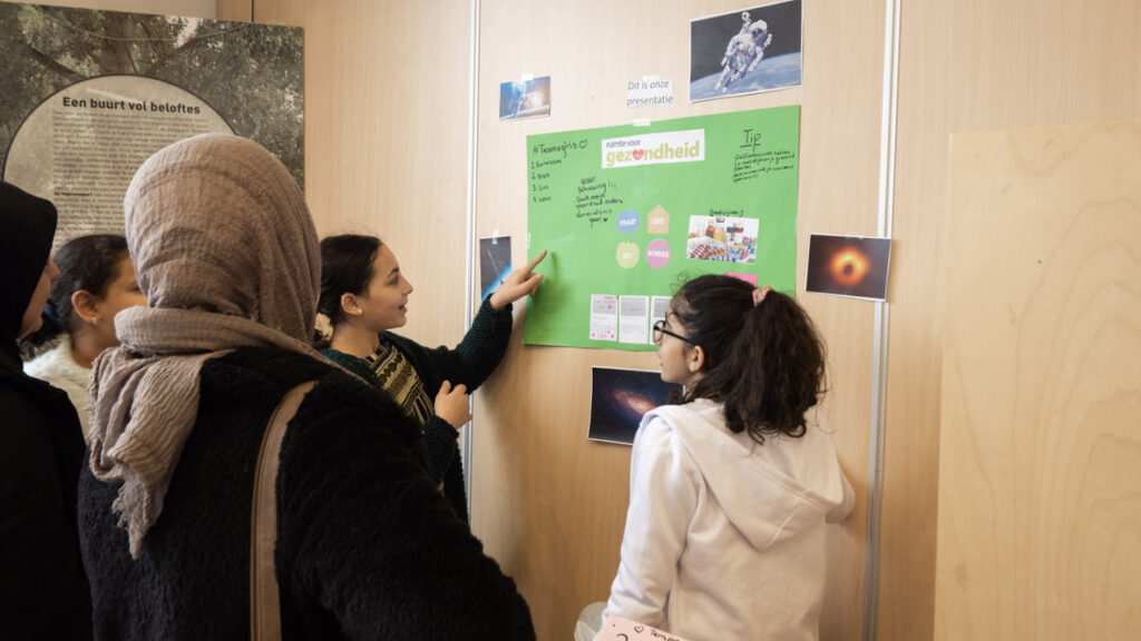 meisjes kijken naar een poster op de muur