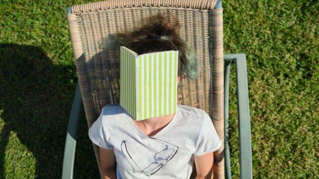 leerling ligt in tuinstoel met haar hoofd onder een opengeslagen boek
