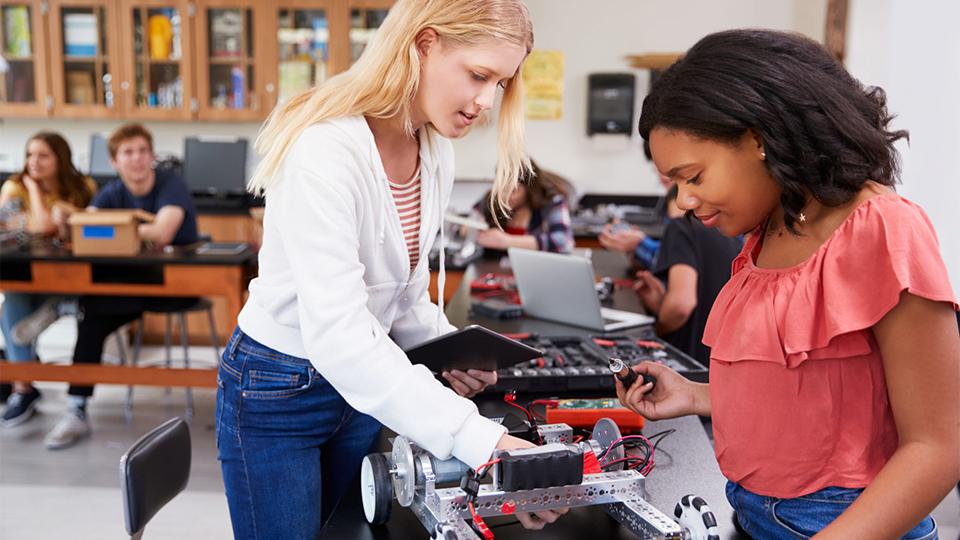 Twee meisjes werken in de klas aan een schaalmodel auto