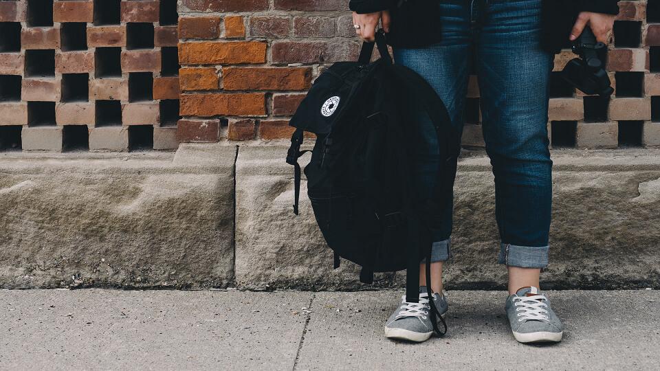 Een leerling met een rugzak in zijn handen.