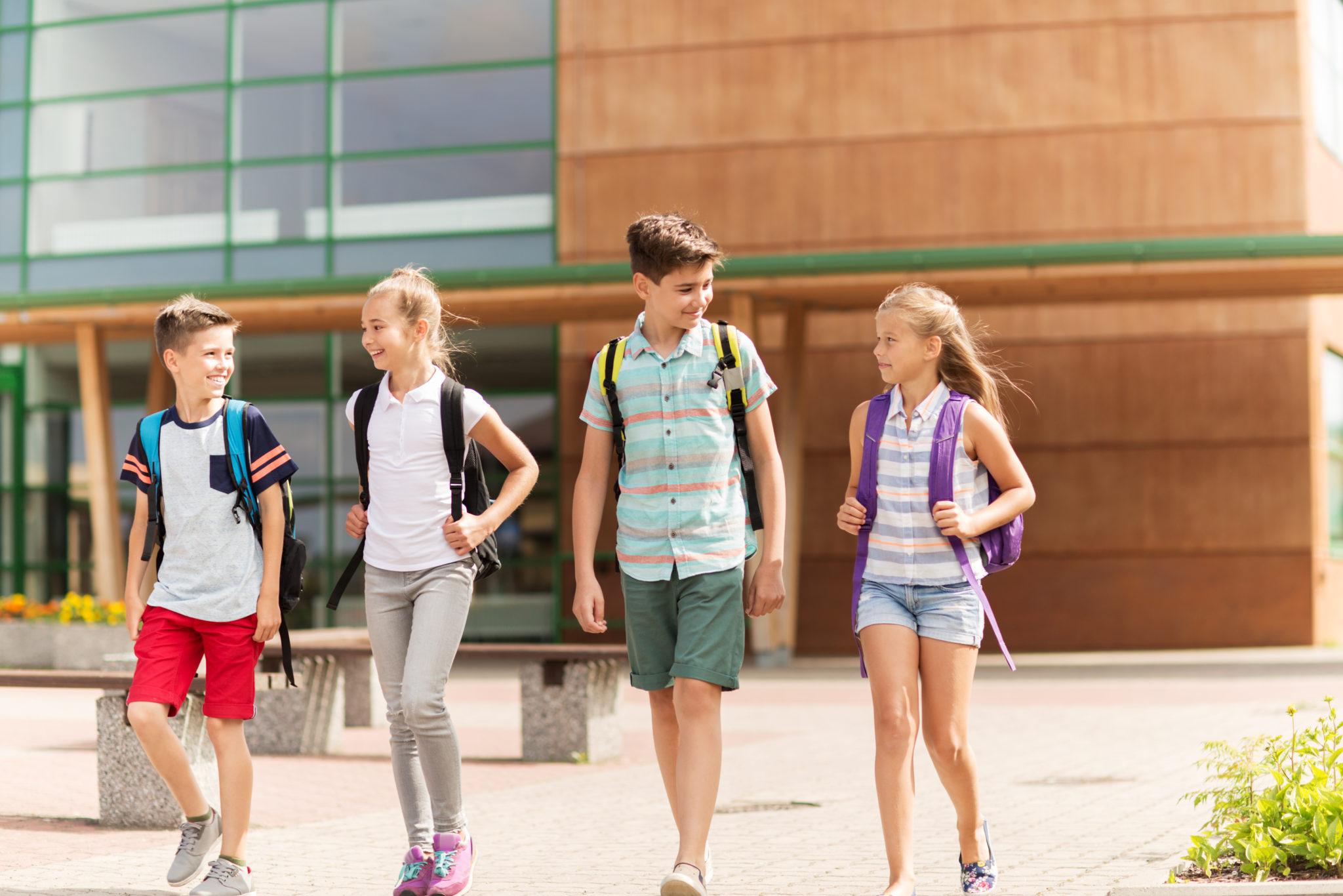 kinderen met rugzak lopen op schoolplein