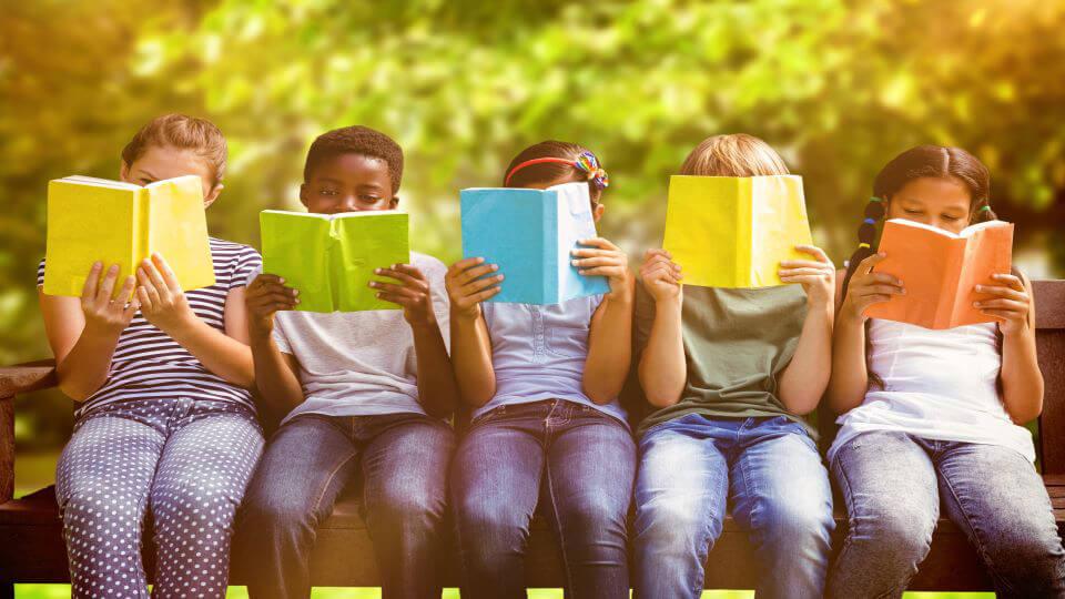 Kinderen zitten op een bankje en houden een boek voor.