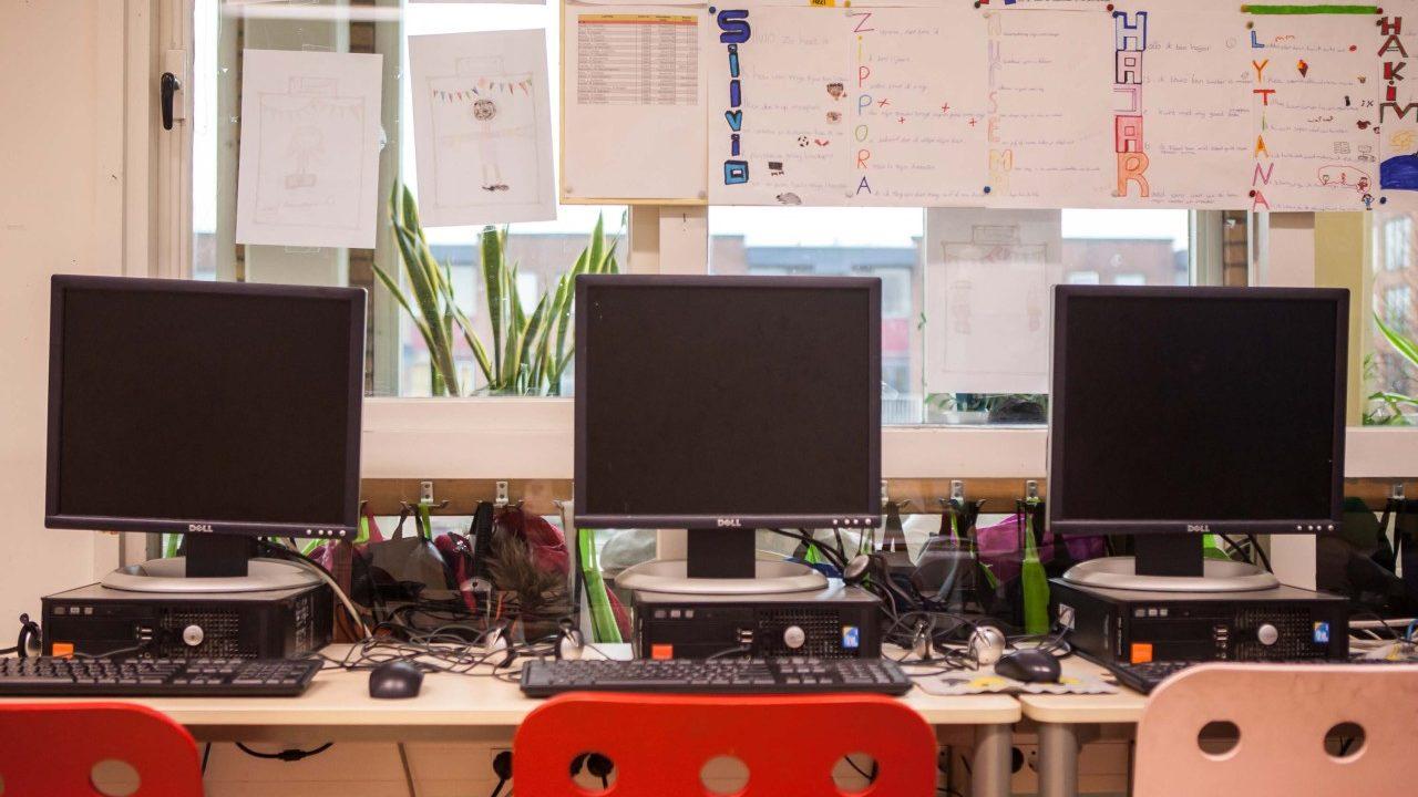 Drie beeldschermen op een tafel in de klas