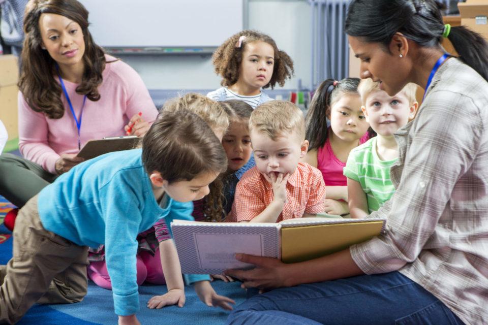 leraar toont prentenboek aan kleuters