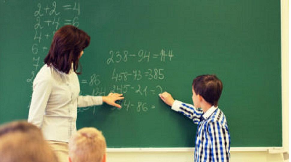 jongen maakt sommen op het schoolbord, lerares kijkt toe