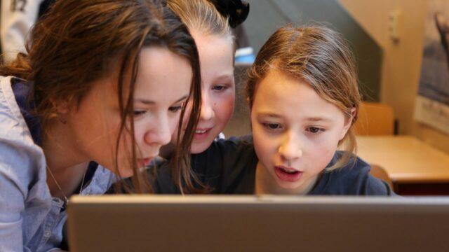 Drie leerlingen kijken samen naar het scherm van een laptop.