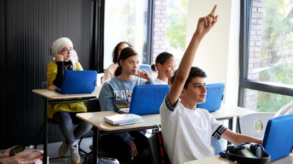 Middelbare schoolleerlingen zitten in een klaslokaal achter hun laptop, een jongen steekt zijn vinger op.