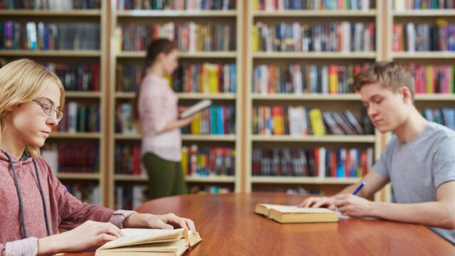Twee studenten zitten in een bibliotheek te lezen