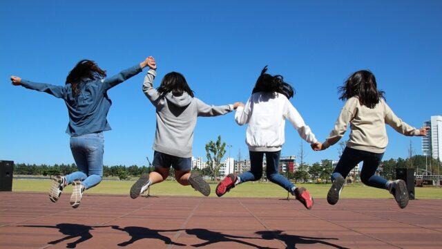 Vier leerlingen houden elkaars handen vast en springen in de lucht.