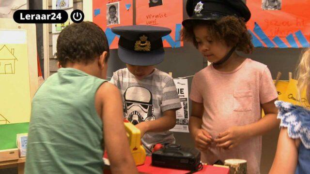 Drie leerlingen spelen in de politiehoek.
