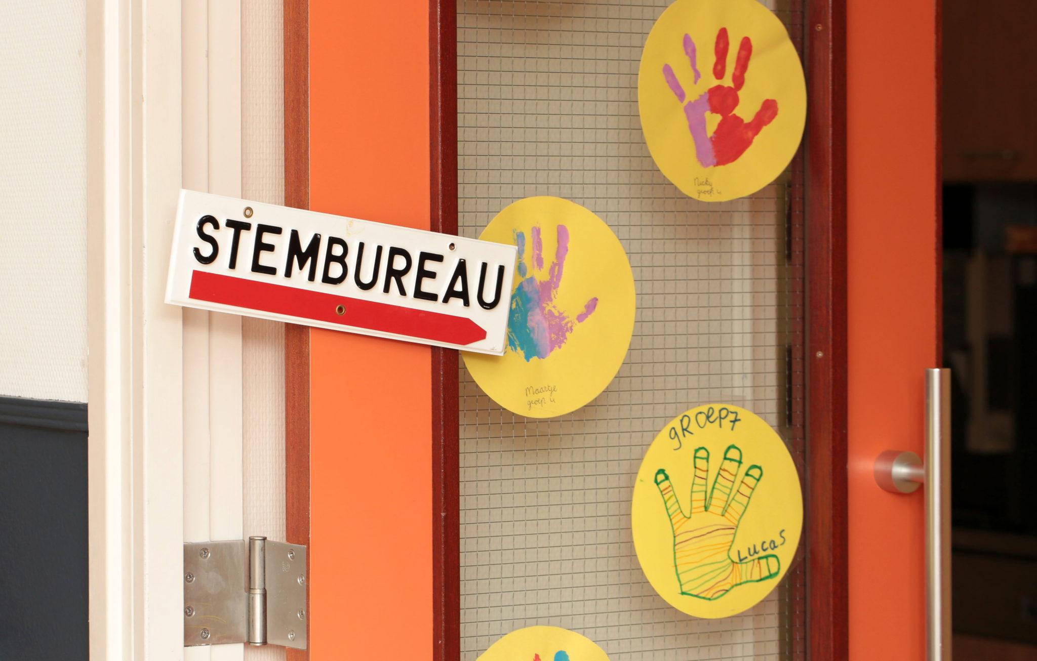 schooldeur met bordje 'stembureau' en knutsels van kinderen