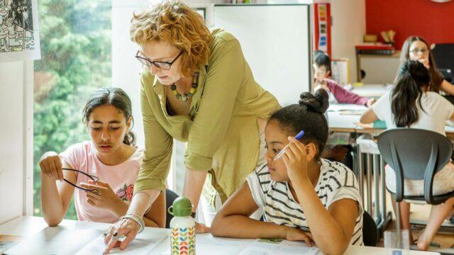 Een leraar geeft uitleg aan twee leerlingen