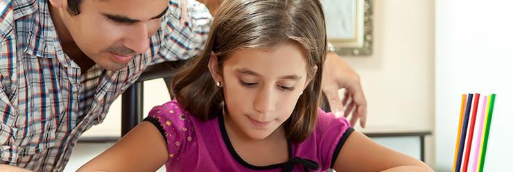 vader helpt dochter met huiswerk