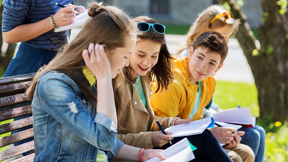 Leerlingen maken een schoolopdracht buiten op een bankje